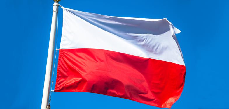 Biało-czerwona flaga Polski, na maszcie, na tle błękitnego nieba